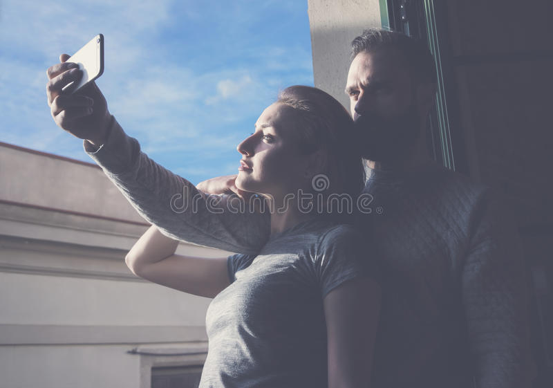 Young couple summer holiday city. Photo woman and bearded man making selfie mobile phone in modern loft. Using royalty free stock images