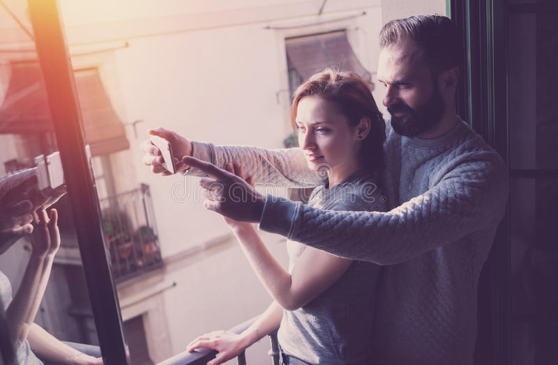 Young couple summer holiday. Photo woman and bearded man making selfie mobile phone in modern loft. Using contemporary royalty free stock photography