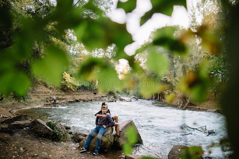 Young couple in the summer on the nature near the river. Love story, appointment, love stock photography