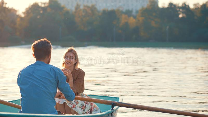 Young couple at sunset. Young couple in a boat at sunset stock photography