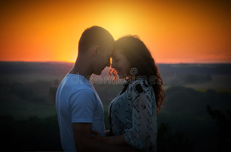 Young couple at sunset on sky background, love concept, romantic people stock image