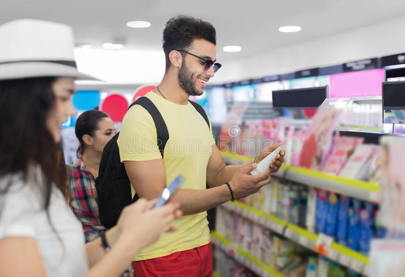 Young Couple In Supermarket Choosing Products Happy Smiling Man And Woman Buying Cosmetics. Shop Interior royalty free stock photos