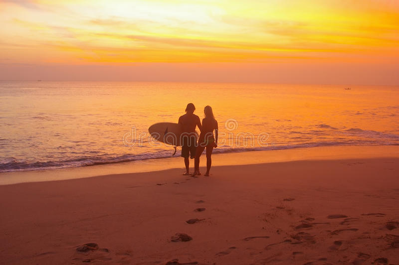 Surfer couple at sunset. Young couple with surfboard Dreamland beach, Bali, Indonesia. Dreamland is one of the most popular surfing areas of Bali stock photo