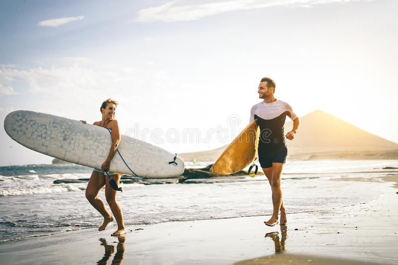 Young couple of surfers running with surfboards on the beach at sunset - Happy lovers going to surf together royalty free stock photos