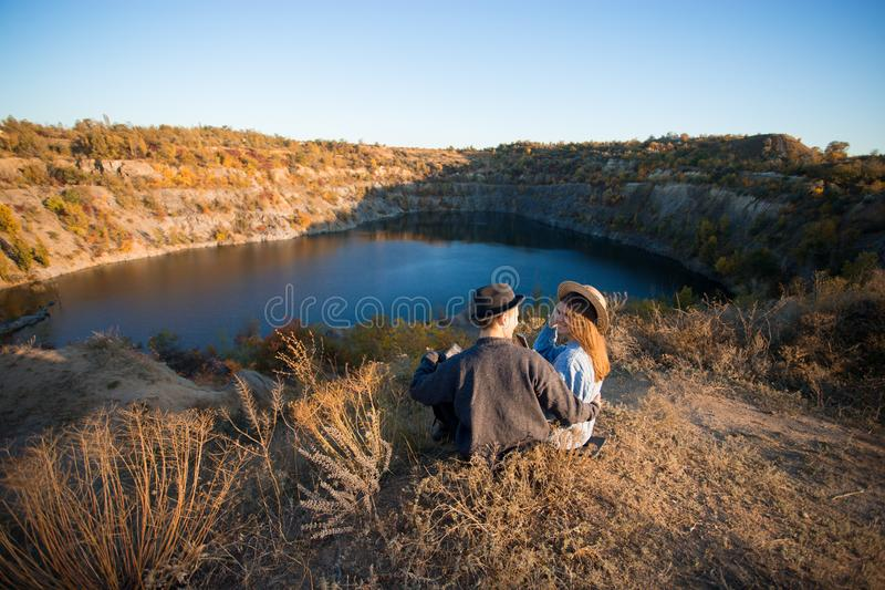 Young couple in sweater and hat sitting near autumn lake smiling having good time stock image