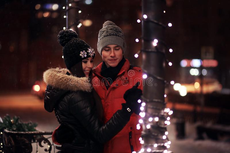 Young couple in sweaters and caps embrace on the winter street. In love in a Christmas garland. St. Valentine`s Day. Young couple in sweaters and caps embrace on royalty free stock photo