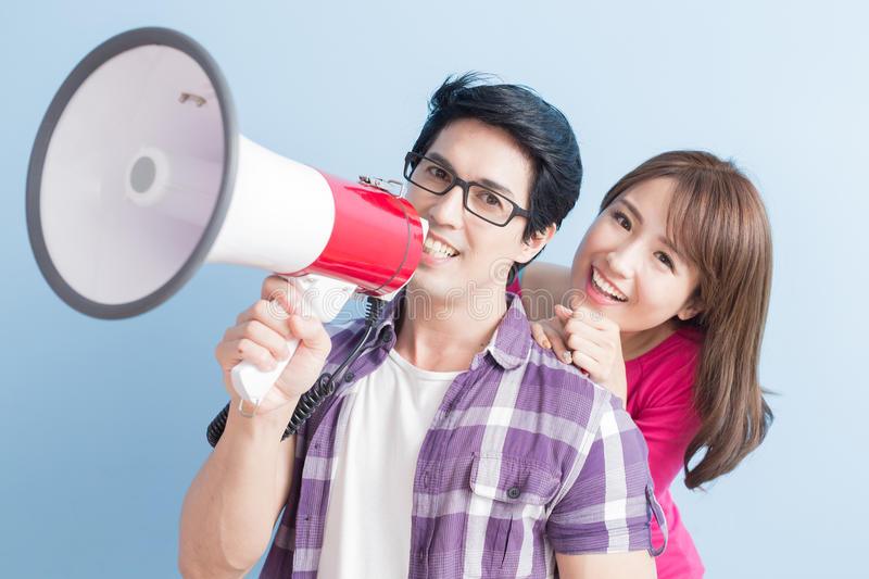 Young couple take the microphone. Shout happily isolated on blue background royalty free stock image