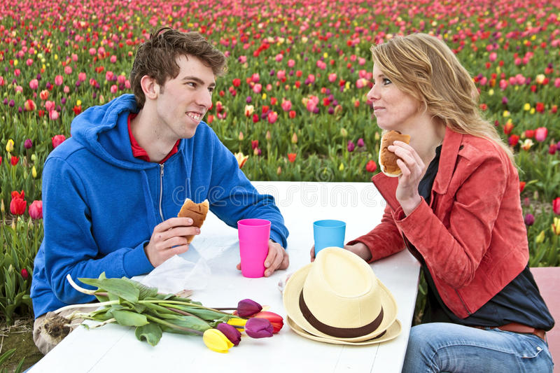 Young couple taking lunch between the tulips royalty free stock photo