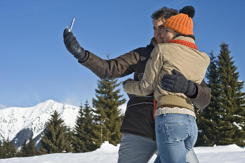 Download Young Couple Taking Photos On The Snow Stock Photo - Image: 27533256