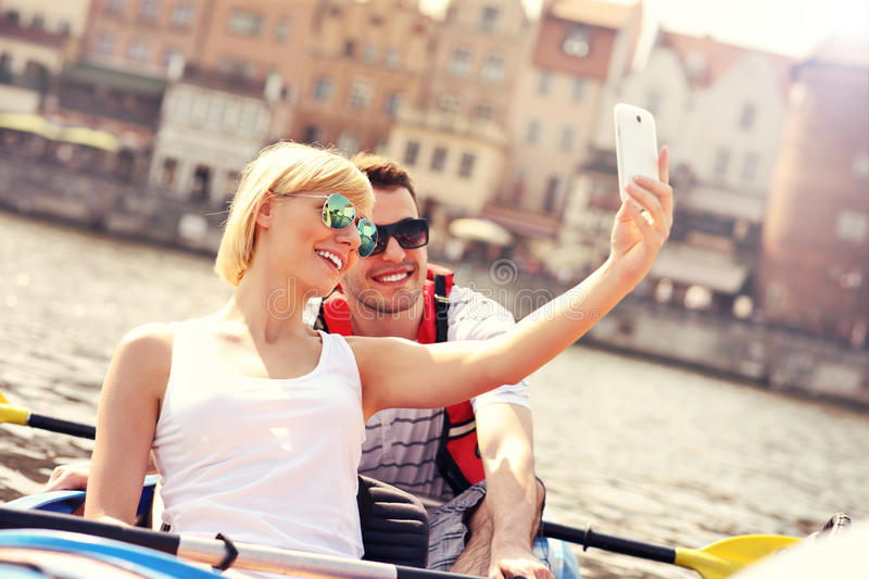 Young couple taking pictures in a canoe stock photos