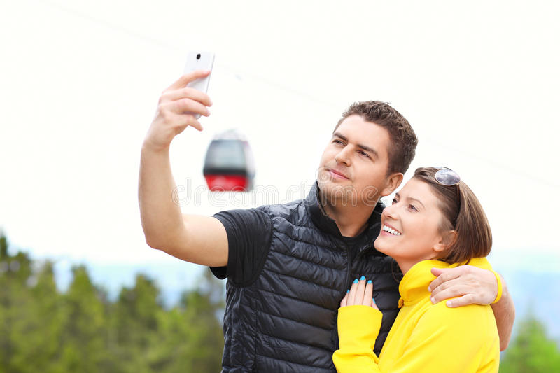 Young couple taking pictures in mountains royalty free stock photo