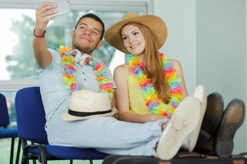 Young couple taking selfie in airport lounge royalty free stock images