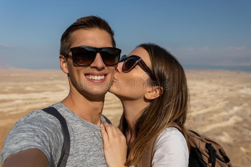 Young couple taking a selfie in the desert of israel. Self portrait picture of a young couple on holiday in Israel, kissing stock photo