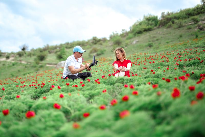Young couple taking selfie on a meadow of wild peonies outdoors. stock photo