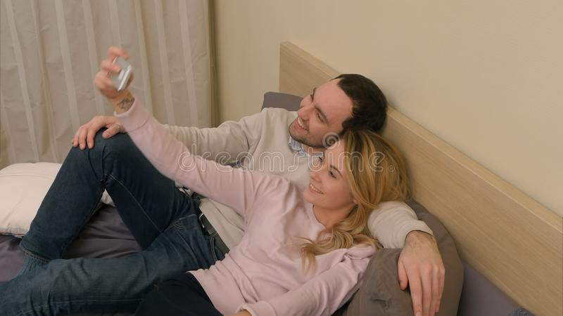 Young couple taking selfie photo using cell phone, lying on bed in bedroom at home royalty free stock photography
