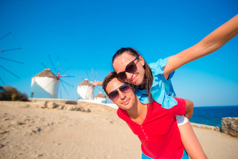 Young couple taking selfie with a stick in front of windmills at popular tourist area on Mykonos island, Greece. Family taking selfie with a stick in front of stock image