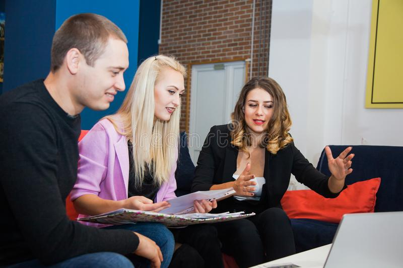Young couple talking to beautiful female manager. Meeting with real estate agent in office, discussing terms of contract royalty free stock image