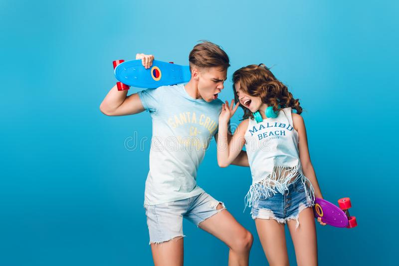 Young couple of teenagers having fun on blue background in studio. They wear T-shirts, jeans shorts, hold skateboards stock photo