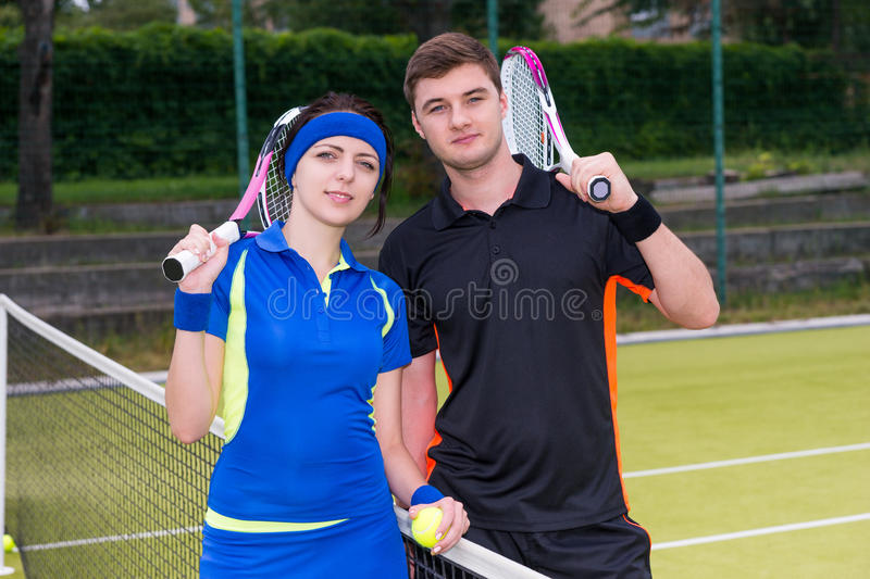 Young couple of tennis players holding a racket and a ball on t royalty free stock photos
