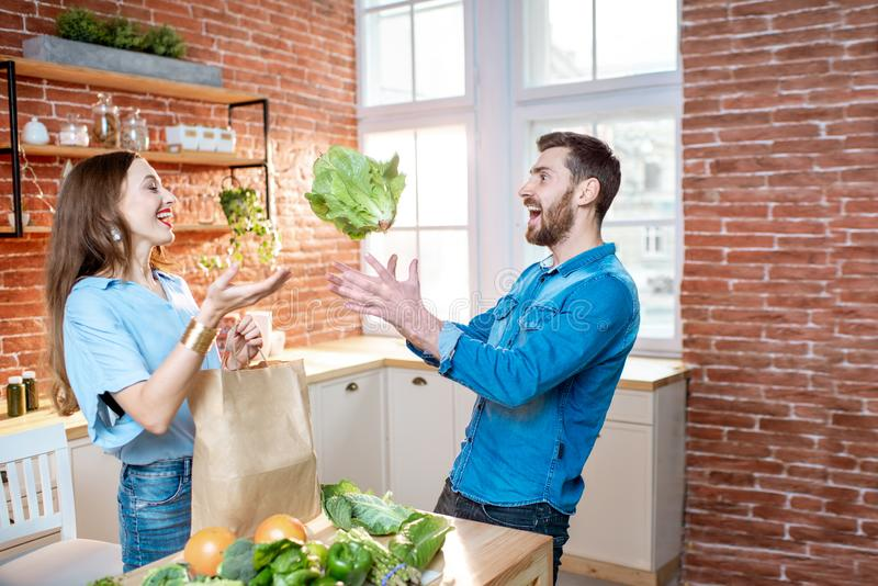 Couple with healthy food on the kitchen. Young couple throwing with fresh cabbage head preparing to cook vegan meals on the kitchen at home stock photography