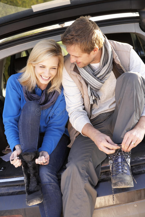 Young couple tie boots at rear of car stock photo