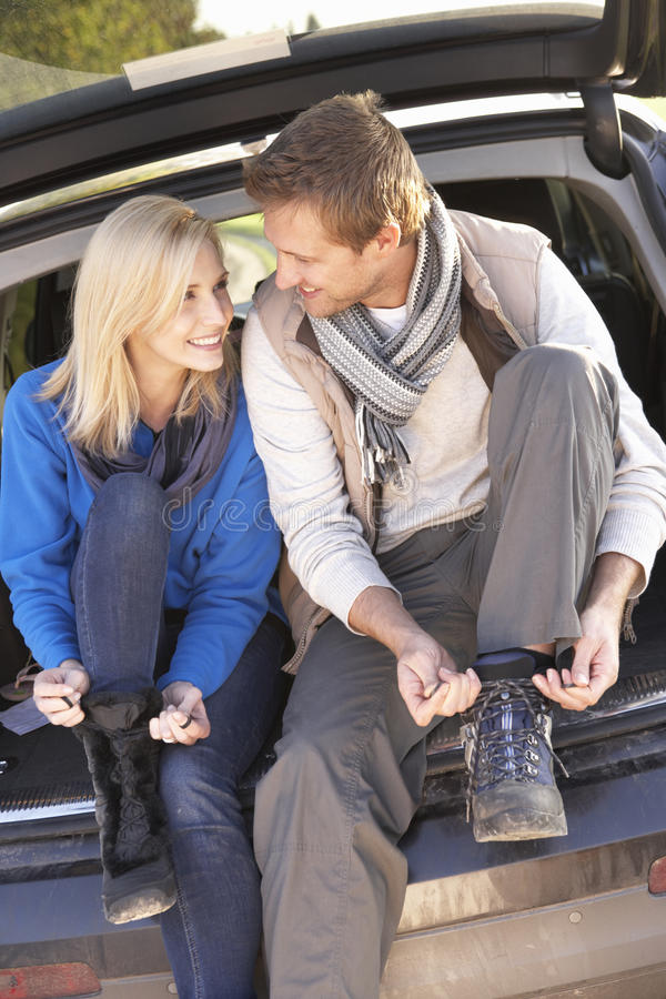 Young couple tie boots at rear of car stock image