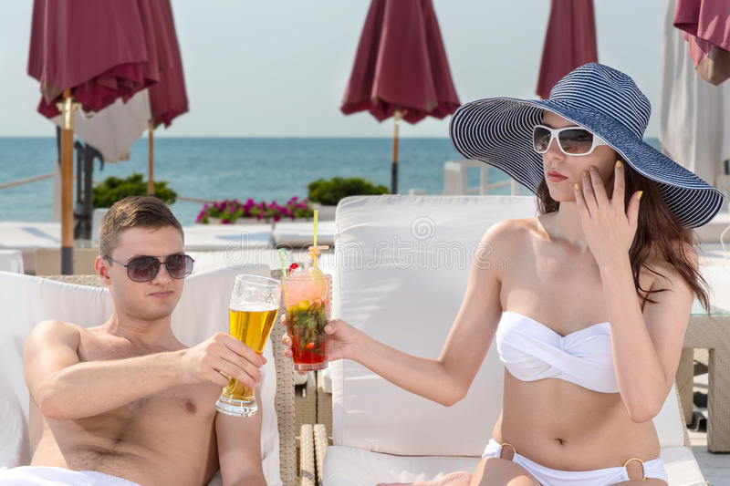 Young couple toasting each other on vacation. Young couple toasting each other with a tropical cocktail and beer as they relax on recliners on the beachfront at royalty free stock photos