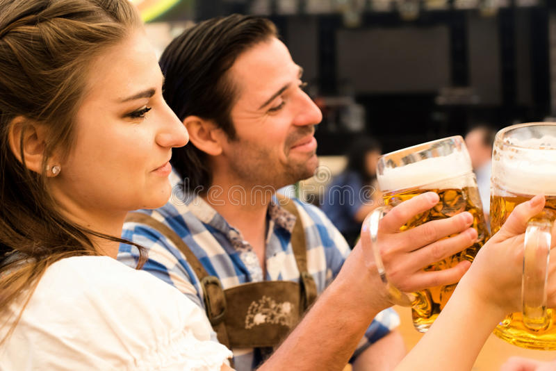 Young couple toasting in Oktoberfest beer tent royalty free stock photos