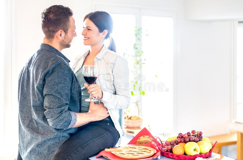Young couple toasting red wine on tender moment at home kitchen - Happy millenial lovers enjoying relax moment cheering together royalty free stock photo