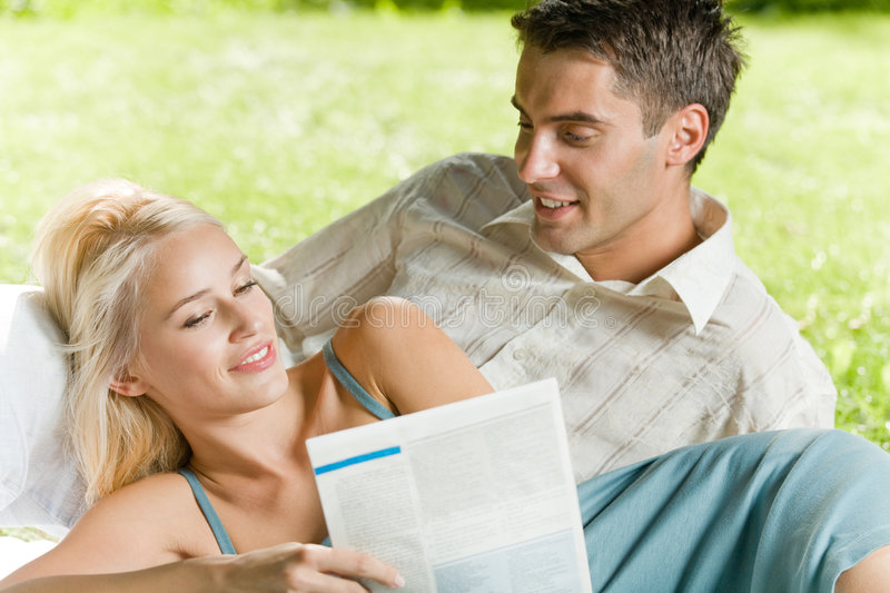 Young couple together. Young couple reading together outdoors royalty free stock photography