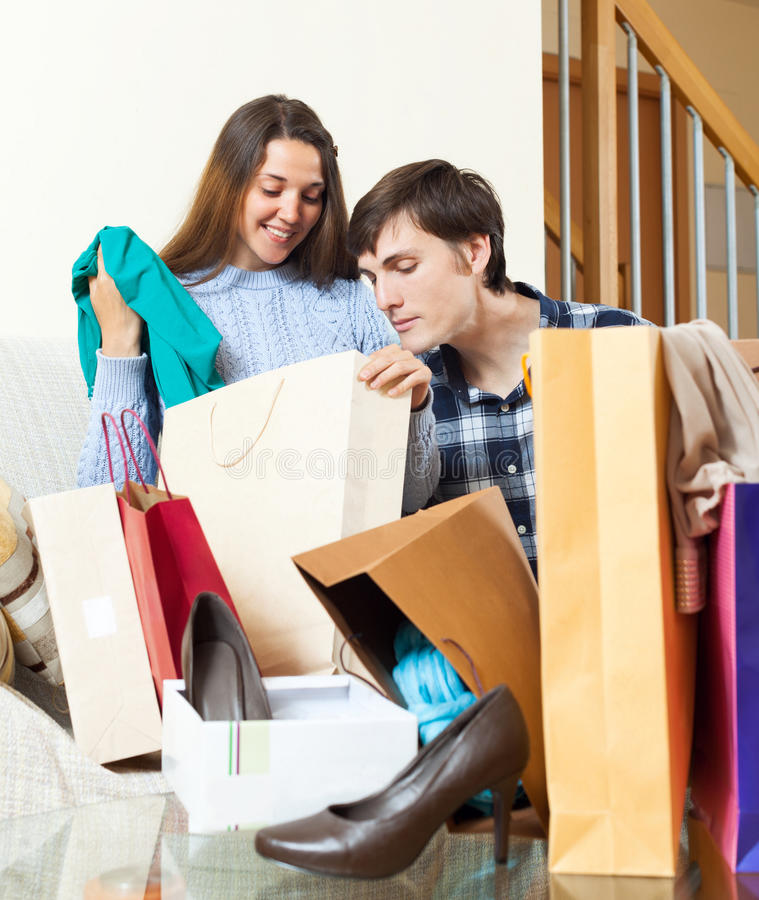 Young couple together with clothes and shopping bags stock images