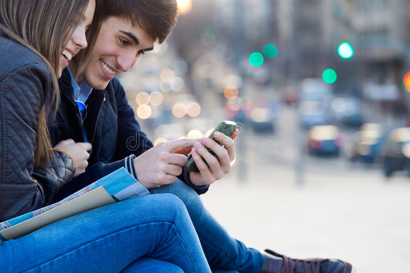 Young couple of tourist in town using mobile phone. stock photography