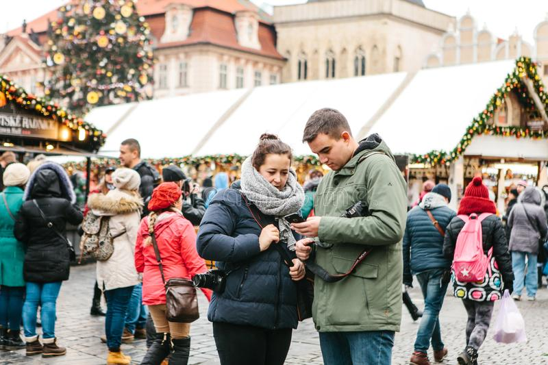 A young couple of tourists looks at a map on a cell phone. Prague, December 25, 2017: A young couple of tourists looks at a map on a cell phone on the main stock image