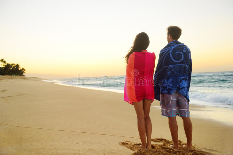 Young couple towels over shoulders in beach sand stock photos