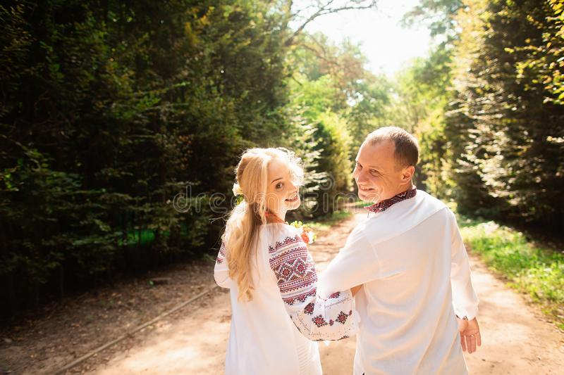 A young couple in a traditional Ukrainian clothing whith bouquet enjoy the sunny day at Stryisky Park in Lviv. Backview stock image