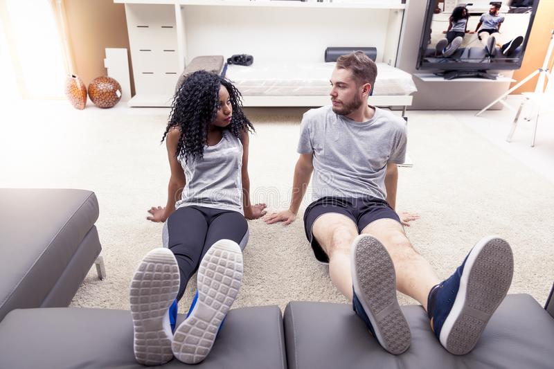 Young couple are training doing gymnastics at home. In a modern apartment stock photo