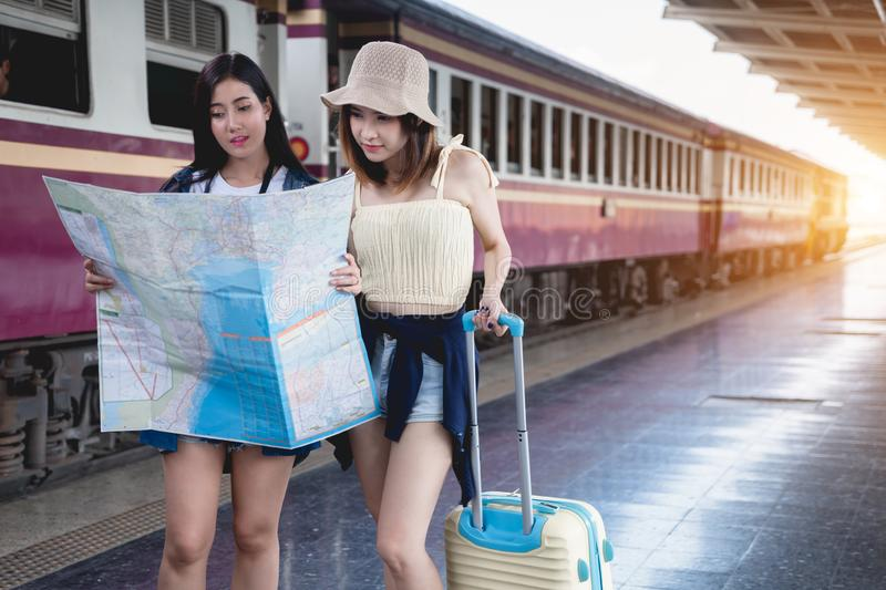 Young couple traveler with map at train station. Asian girls lost at railway in summer on vacation. women lifestyle adventure stock photography