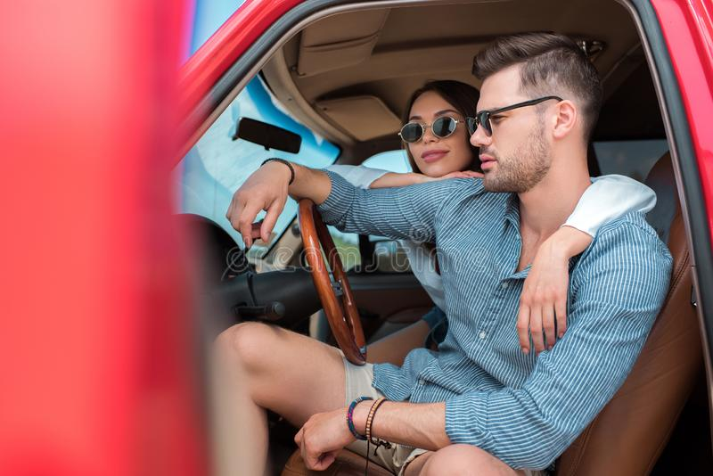 Young couple of travelers in sunglasses sitting in car. And hugging together stock photography