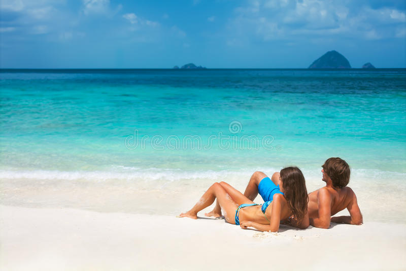 Young couple on the tropical beach. Young couple relaxing on the tropical sea paradise stock photos