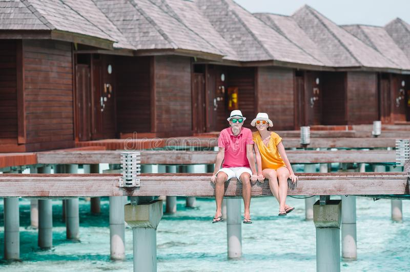 Young couple on beach jetty at tropical island in honeymoon royalty free stock photos