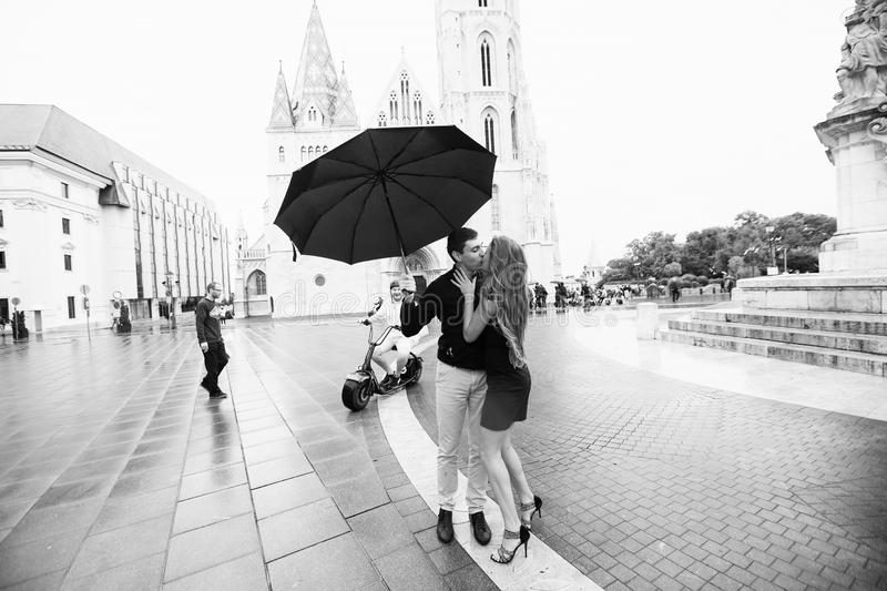 Young couple with umbrella walking in Budapest on a rainy day. Love story. Black and white royalty free stock images