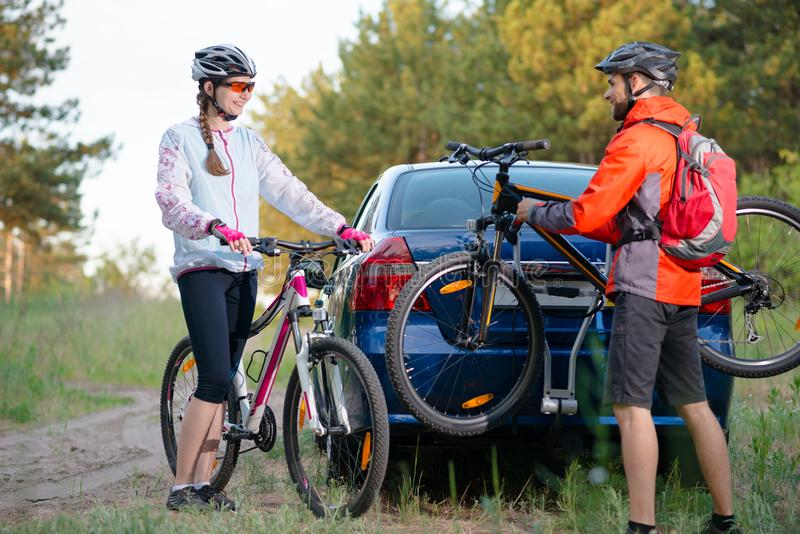 Young Couple Unmounting Mountain Bikes from Bike Rack on the Car. Adventure and Family Travel Concept. royalty free stock photo