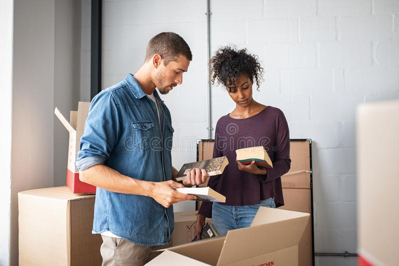 Young couple unpacking books from cardboard boxes royalty free stock images