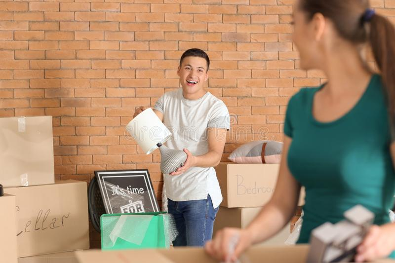 Young couple unpacking boxes indoors. Moving into new house stock photo