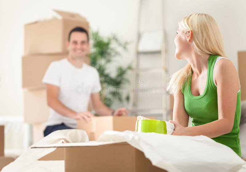 Young couple unpacking moving boxes stock photo