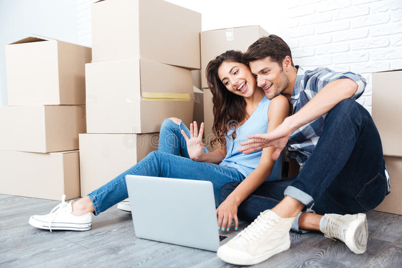 Young couple using laptop and showing keys. To web camera while moving in new flat stock photo