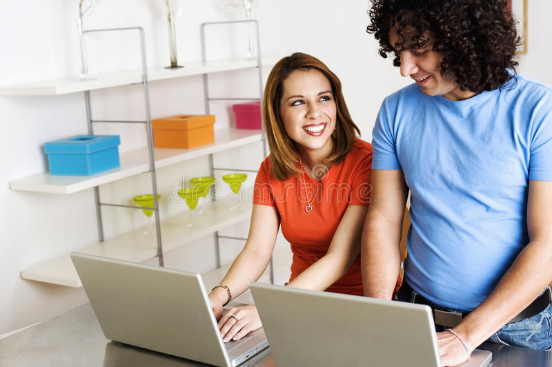 Download Young Couple Using Laptops And Smiling Stock Image - Image: 13649365