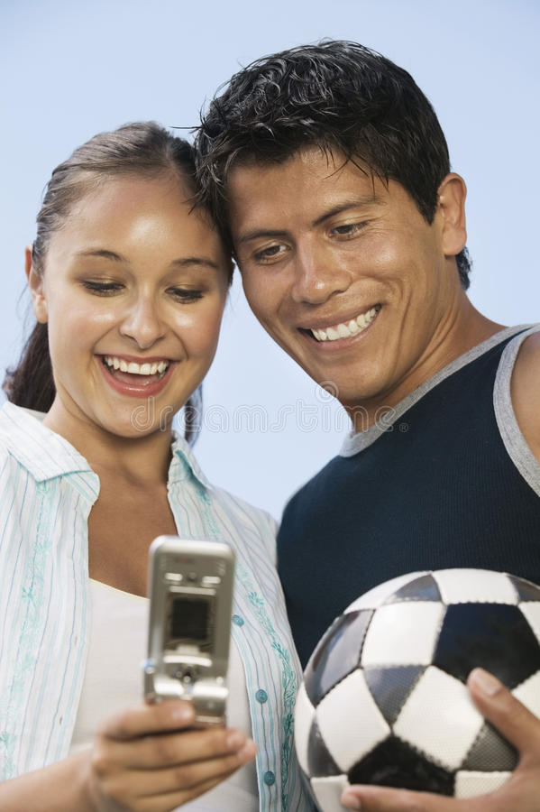 Young Couple Using Mobile Phone With Soccer Ball stock photography
