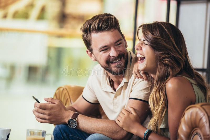Young couple using a smartphone and smiling while sitting in the cafe stock photos