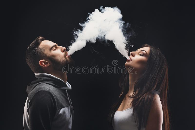 Young couple vaping e-cigarette with smoke on black closeup. Couple vaping. Young men and women blowing smoke to join it in one cloud at black studio background stock image